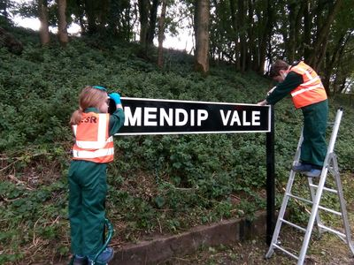 the completed sign being erected by Toby and Anwen
