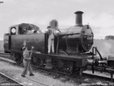 Jinty 47493 seen taking on some more unleaded fuel (water) at Cranmore West Halt, with fireman Pat Goodfellow inspecting the water