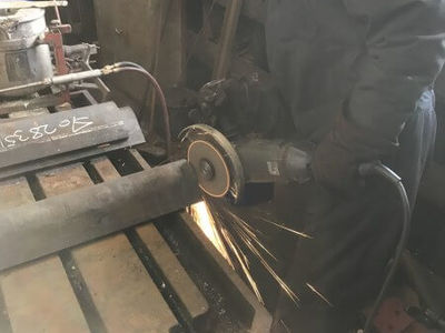 Phil grinds the ends of the new tank supports. These are 20mm thick sections folded into a right angle. They will have end plates welded on before being machined square and then drilled and riveted back onto the frames.