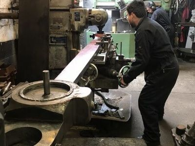 mounted on the milling machine to have the bores trued up. Here Matt machines the right hand leading bore. In the background Elliot is finishing off one of the rocker bearings in the borer.