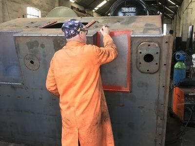 The bunker was turned over so that Jeff could finish welding the underside. He is seen here applying some primer paint.