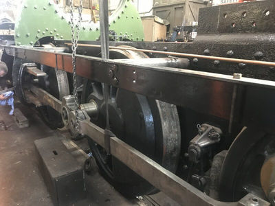 The left hand coupling rods are all joined together and then lifted and fitted to the crank pins. Each wheel is rotated to get them aligned so that the rods fit.